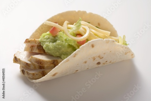 Folded tortilla filled with chicken, guacamole and cheese