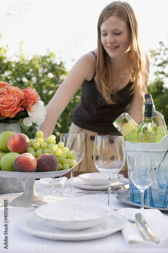 Woman by table laid in garden