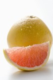 Wedge of pink grapefruit in front of whole grapefruit