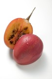 Tamarillo with drops of water, halved