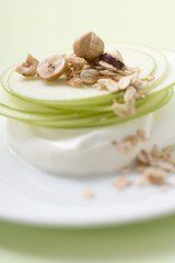 Yoghurt with apple slices, rolled oats and hazelnuts