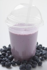 Blueberry shake in plastic cup, surrounded by blueberries