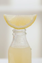 Lemon juice in bottle with fresh lemon wedge