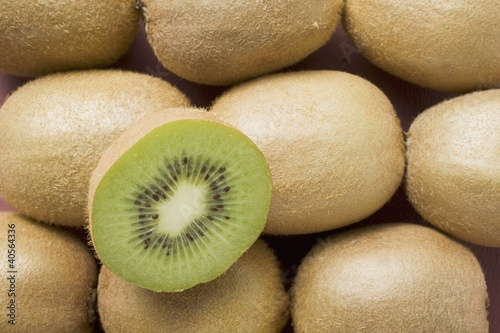 Half a kiwi fruit on several whole kiwi fruits