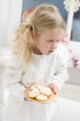 Small girl with angel's wings holding plate of biscuits