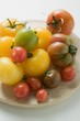 Various types of tomatoes on wooden plate