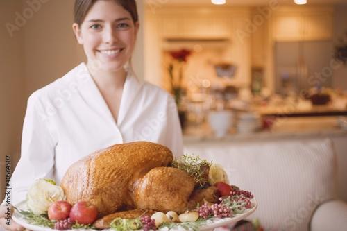 Young woman serving roast turkey on platter