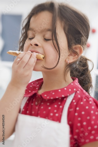 Small girl eating Christmas biscuit she has made herself