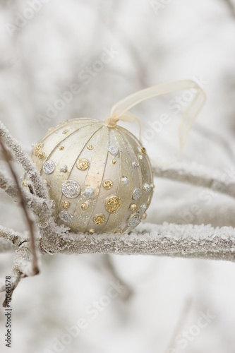 Christmas bauble on frost-covered branch out of doors