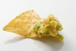 Guacamole on nacho (close-up)
