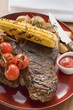 Grilled steak, corn on the cob, cherry tomatoes, potatoes, ketchup
