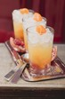 Three fruity drinks with orange and pomegranate
