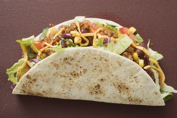 Taco filled with mince & cheese on brown background