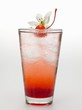 Tequila Sunrise with ice cubes, cocktail cherry and flower