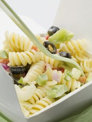Fusilli with vegetables in take-away container (close-up)