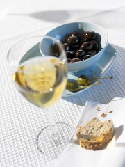 Olives, capers, bread and glass of white wine