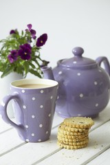 Teapot, mug of tea, fruit shortcakes and pansies