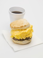 Scone filled with scrambled egg, cheese & sausage, cup of coffee