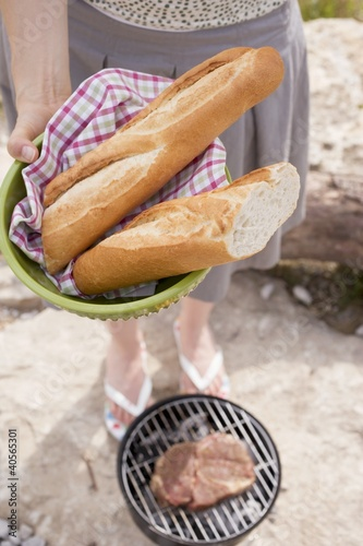Woman with baguettes at a barbecue on a river bank