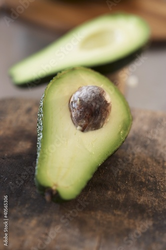 Avocado, halved, on old chopping board