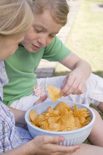 Two girls eating crisps out of doors
