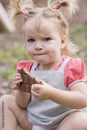 Little girl holding part of a bar of nut chocolate