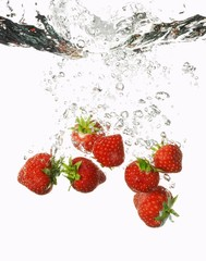 Strawberries falling into water