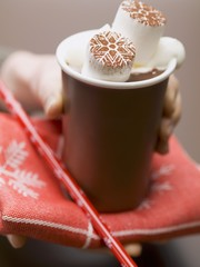 Hand holding beaker of hot chocolate with marshmallows & cream