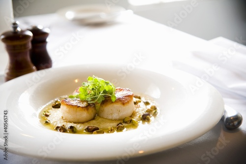 Seared Scallops in White Dish on Restaurant Table