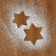 Star shapes in icing sugar on wooden background