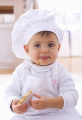 Little girl in chef's hat eating biscuit