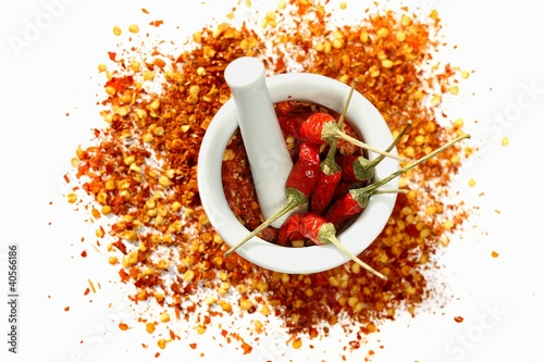 Dried chilli peppers and chilli flakes in a mortar