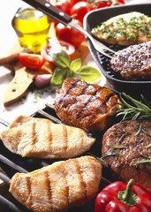 Various meats on barbecue and in grill frying pan