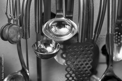 Different kitchen utensils hanging from hooks in a kitchen