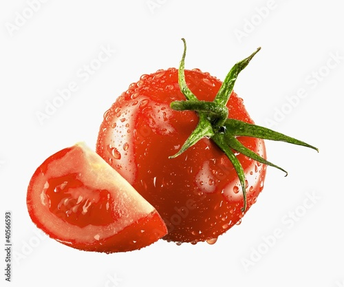 One whole and one tomato wedge with drops of water