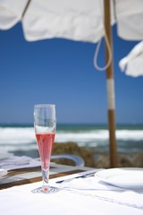 Sangria in sparkling wine glass on table on beach