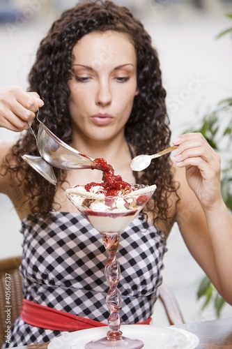 Woman pouring hot raspberries over vanilla ice cream