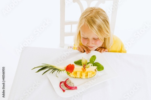 Girl sitting at table in front of plate of fruit