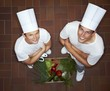 Two chefs with their arms folded beside crate of vegetables