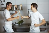 Two chefs fencing with wooden spoons in commercial kitchen