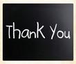 """Thank you"" handwritten with white chalk on a blackboard"