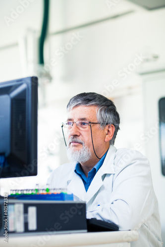 Senior researcher working on a computer in a lab