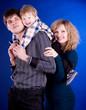 Family with baby boy on blue background