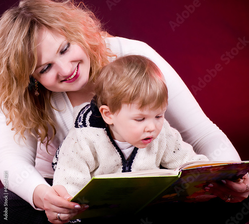 Mother and baby boy reading book and smiling