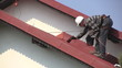 Man paints roof of a private house
