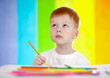 Redheaded adorable boy drawing with yellow pencil on rainbow bac