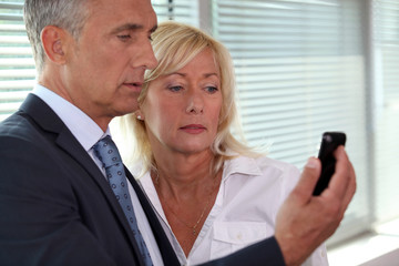 mature businessman showing his blonde wife sms