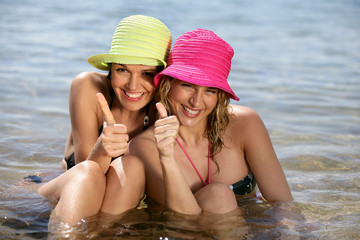Two woman sat in the sea giving thumbs-up