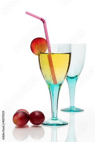 Cocktail still life with colored glass, drink and grapes