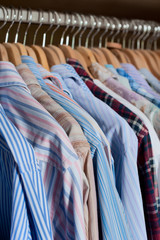 Selection of men's shirts hanging inside a wardrobe